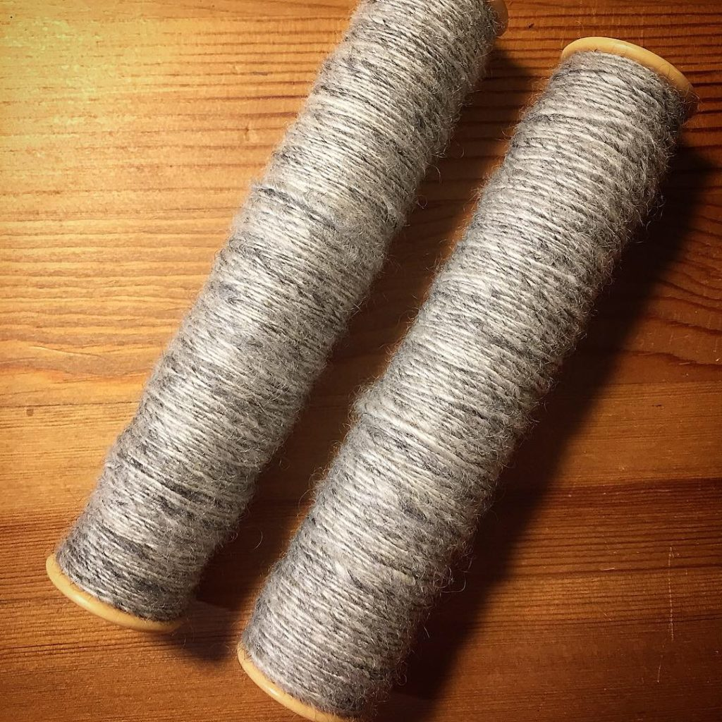 Two weaving bobbins wound with grey singles yarn.